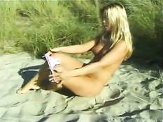 Блондинка раздевается и ласкает себя на пляже