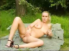 Блондинка раздевается и показывает свою киску в лесу