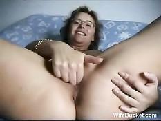 Жена в очках раздвигает ноги и ласкает волосатую киску и грудь