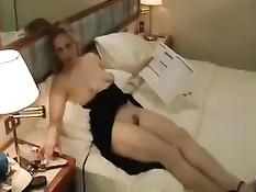 Мишель на кровати задирает своё чёрное платье и показывает грудь