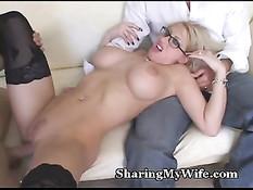 Грудастая блонда в очках на диване развлекается с двумя парнями