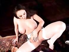 Очаровательная шатенка с большой грудью надевает на полу чулки