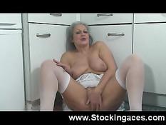 Зрелая дама в белых чулках раздевается и мастурбирует на кухне
