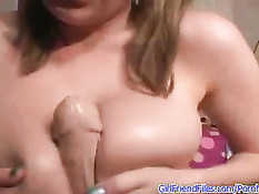 Девушка показывает свои большие сиськи и сжимает ими вибратор