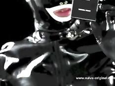Рабыня в маске и латексном костюме вылизывает ноги своей госпоже