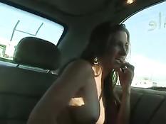 Голая тёлка сидит на заднем сиденье машины и мастурбирует вибратором