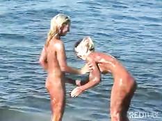Две молодые блондиночки вымазались в шоколаде на морском пляже