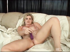 Блондинка в постели играет с большими сиськами и фаллоимитатором