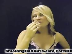 Блондинка с пирсингом в носу выкуривает сигарету в нижнем белье