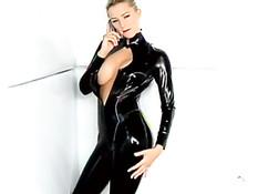 Красивая девушка позирует в латексном костюме и показывает грудь