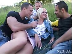 Парни втроём оттрахали молодую блондинку в густой траве на поле