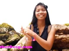Азиатская девчонка на камнях на берегу мастурбирует бритую писю