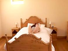Молодая девчонка на кровати надевает на себя наручники и кляп