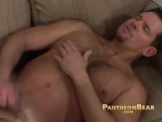 Зрелый гей в бейсболке снимает джинсы и дрочит член на диване