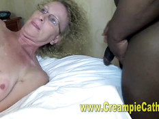 Кудрявая дамочка в очках трахается с двумя мужчинами на кровати