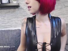 Девушка с красными волосами позирует в чёрном латексном наряде