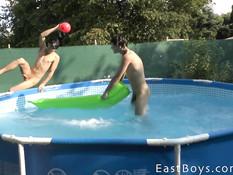 Двое голубых парней летом купаются голышом в открытом бассейне