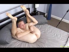 Гей с очень гибким телом на кровати отсасывает собственный член