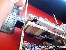 Продавщица в чёрных трусиках задирает юбку и показывает киску