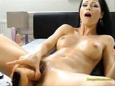 Молодая брюнетка вставляет в киску дилдо и мастурбирует руками