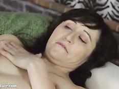 Татуированная зрелая брюнетка раздевается и мастурбирует рукой