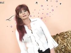 Пожилая женщина с рыжими волосами раздевается и мастурбирует