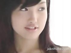Застенчивая японская милашка прикрывает руками большую грудь