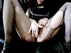 Девушка гот в рваных сетчатых колготках теребит побритую пизду