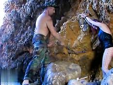 Мужик ебёт привязанную к камню рыжую рабыню в сетчатых чулках