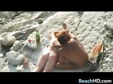 Семейная пара загорает на морском пляже и ласкает друг дружку