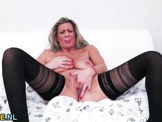 Голландская зрелая блондинка мастурбирует киску в чёрных чулках