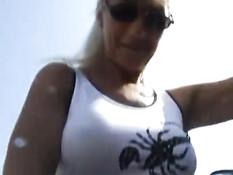 Блондинка в солнцезащитных очках на улице оголяет грудь и пизду