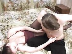Молодой любовник трахает на кровати зрелую брюнетку в колготках