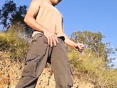 Очкарик гей достаёт из штанов свой член и надрачивает на природе