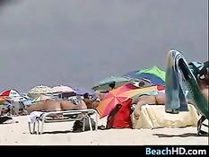 Обнажённая сиськастая брюнеточка загорает на пляже с подружкой