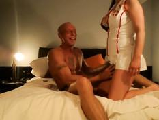 Грудастая медсестра в латексном халате трахает мужика страпоном
