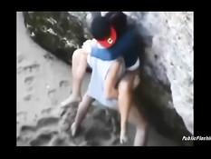 Возбуждённая молодая пара занимается сексом на пляже за камнями