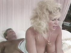 Пышногрудая блондинка сосёт у любовника член и трахает его в постели