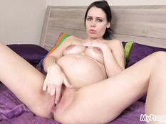 Голубоглазая беременная брюнетка мастурбирует киску лёжа на кровати