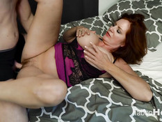 Развратная рыжая мамочка с большой грудью трахается с молодым парнем