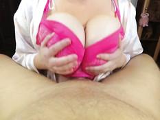Девушка в розовом лифчике зажимает член между больших сисек и дрочит