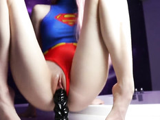 Красивая русская девчонка в костюме супермена трахает себя фаллосом