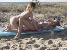 Две молодые блондинки лесбиянки ласкают друг дружку на морском пляже