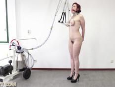 Связанная рыжая девушка с кляпом во рту испытывает доильный аппарат