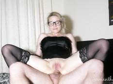 Очкастая блондинка в чёрных чулках насаживается своим анусом на член