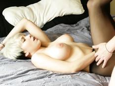 Сисястая молодая блондинка в чёрных колготках ебёт парня на кровати