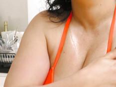 Вымазавшаяся маслом сисястая зрелая брюнетка трахает себя вибратором